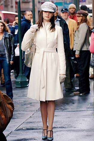 DWP-129 AndyÕs (Anne Hathaway) outfit features wool belted cream felt overcoat; nubby tweed newsboy style cap by Chanel; Calvin Klein gold snakeskin satchel and grey tweed Marni shoes with dark brown leather trim, and high heeled pumps with t-straps. PHOTOGRAPHS TO BE USED SOLELY FOR ADVERTISING, PROMOTION, PUBLICITY OR REVIEWS OF THIS SPECIFIC MOTION PICTURE AND TO REMAIN THE PROPERTY OF THE STUDIO. NOT FOR SALE OR REDISTRIBUTION.