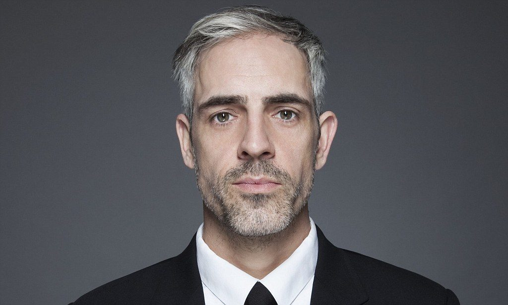 Man with graying hair in black suit