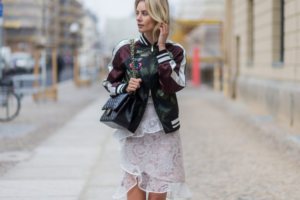 BERLIN, GERMANY - JANUARY 20: Lisa Hahnbueck wearing Velention Satin Bomber Jacket with Butterfly Patches, Self-Portrait Lace Skirt with Frilles, Chanel Timeless Flap Bag, VANS Sk8-Hi during the Mercedes-Benz Fashion Week Berlin A/W 2017 at Kaufhaus Jandorf on January 20, 2017 in Berlin, Germany. (Photo by Christian Vierig/Getty Images)